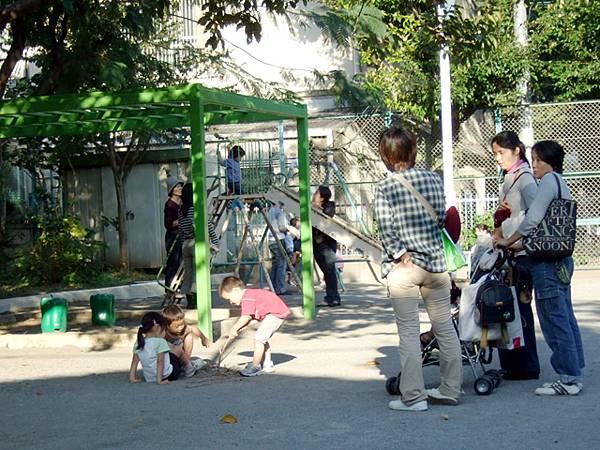 主婦們帶著自家小朋友來公園玩,自己則和其它媽媽在大聊八卦