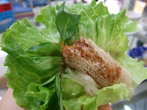 附上生菜和九層塔包著春捲享用,吃的時候別忘了沾點特製醬汁