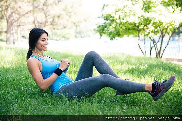 smiling-sporty-woman-doing-stretching-exercsises-on-the-green-grass-in-park_BFWZKfzABo.jpg