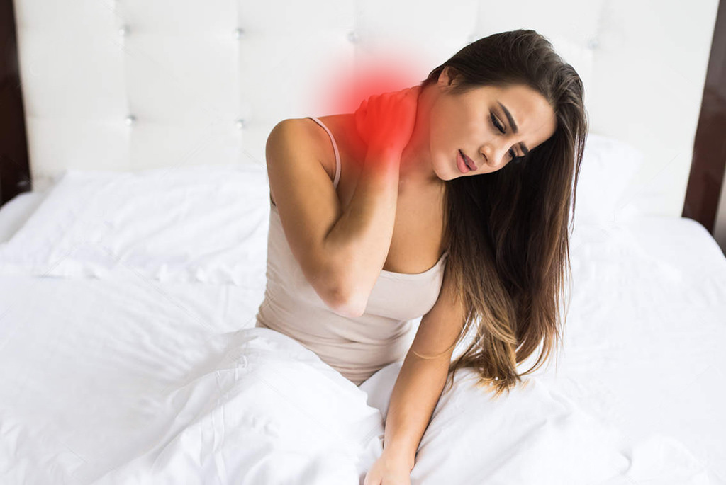 Young woman sitting on the bed with pain on neck