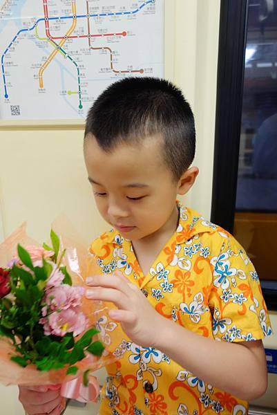 弟弟在捷運上把玩姊姊的花束