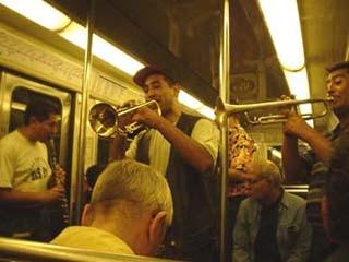 正在地鐵車箱裡忘情吹彈異國情調的走唱藝人