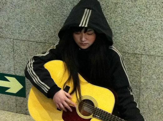 乞丐蘿莉 坐在冰冷的地上抱著吉他,手指都已經凍的泛紅。」