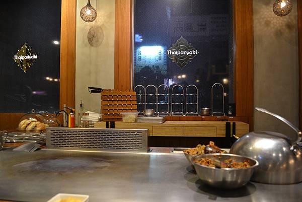 窗戶上印有店名Thaipanyaki,鐵板上則放著辣與不辣的打拋豬肉