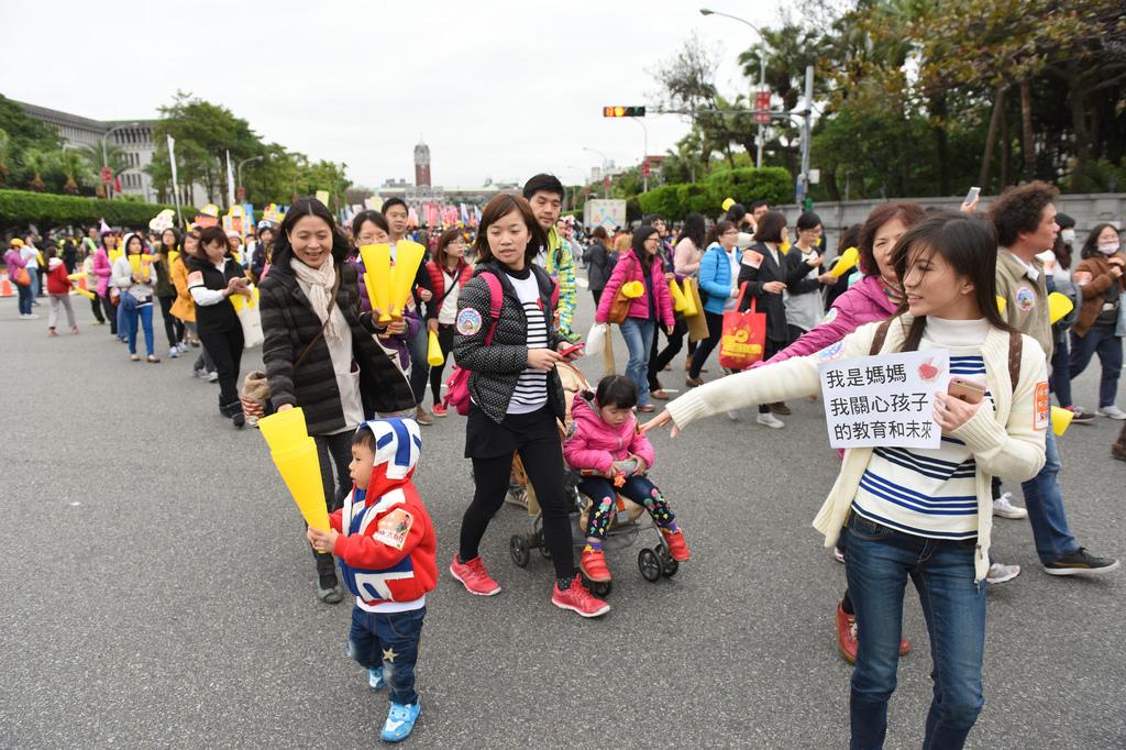 家長帶著小孩加入支持幼教公共化的遊行行列
