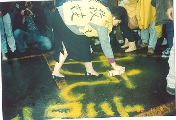 華西街遊行-領隊之一在警察局門口地上噴上抗議字眼.jpg