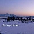 房間外夕陽西下的雪景。