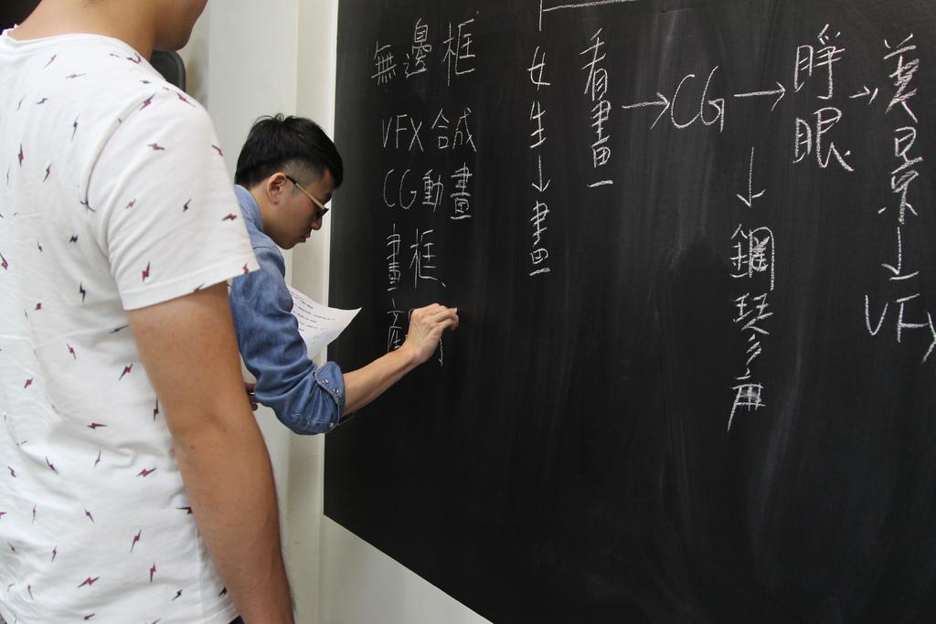 技術人員加入影片所需要的內容,導演在旁構想影片畫面.JPG