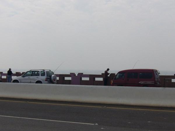 一堆人把車停了,就在橋上釣魚
