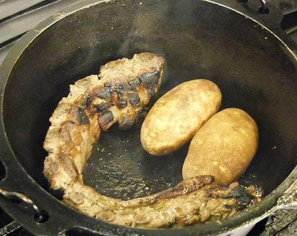 將抹過海鹽的豬肋排與馬鈴薯放入鑄鐵鍋烤