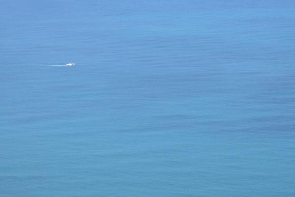 海藍的沒有其他顏色  只有一艘小船泊過