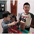 三個小孩擠在一起看禮物