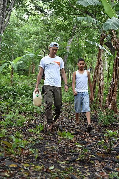資助兒童計畫代言人楊祐寧陪伴12歲的尼爾森(Nielson)步行在濕滑的山路上前往取水點。(台灣世界展望會提供)