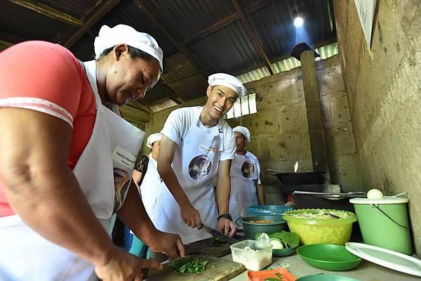 楊祐寧戴上廚師帽、穿上圍裙,和尼加拉瓜社區媽媽一起以豆子、蔬菜、玉米、雞蛋等,製成營養美味的「大鍋飯」。(台灣世界展望會提供)