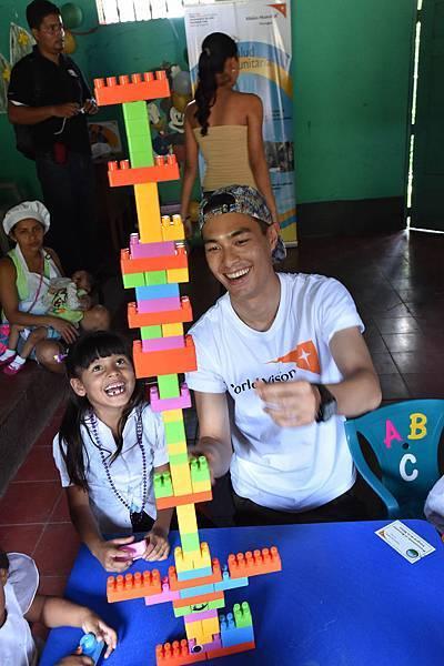 台灣世界展望會資助兒童計畫代言人楊祐寧在尼加拉瓜的兒童營養中心陪伴孩子一起玩玩具。(台灣世界展望會提供)