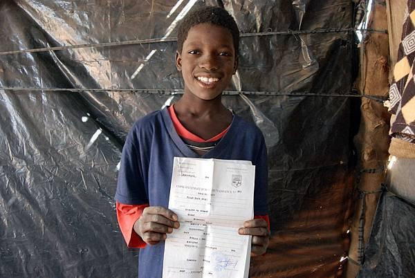 8歲的奧斯曼,拿著新辦妥的出生證明,開心準備上學去-台灣世界展望會提供
