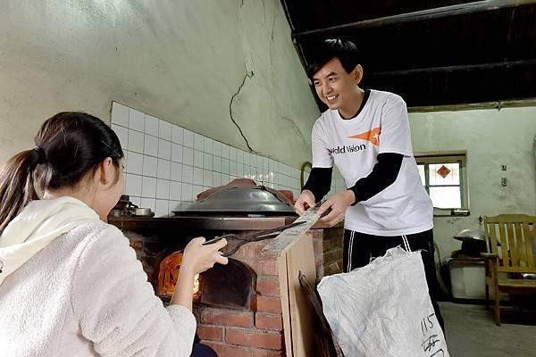 黃子佼幫助小安在沒有熱水器的家添柴燒洗澡水(台灣世界展望會提供).jpg