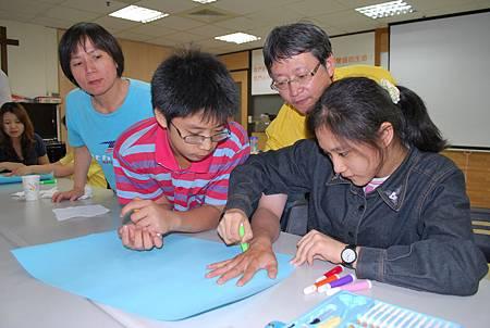 東高雄聖教會林信榮與洪嫦羚牧師夫婦一家人照顧兩位寄養家庭兒童,現場一起畫圖同樂-台灣世界展望會提供.jpg