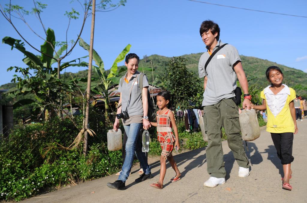 02代言人何潤東、張鈞甯與胡氏娟(右一)及妹妹(左一)一起提水回家-台灣世界展望會提供.JPG