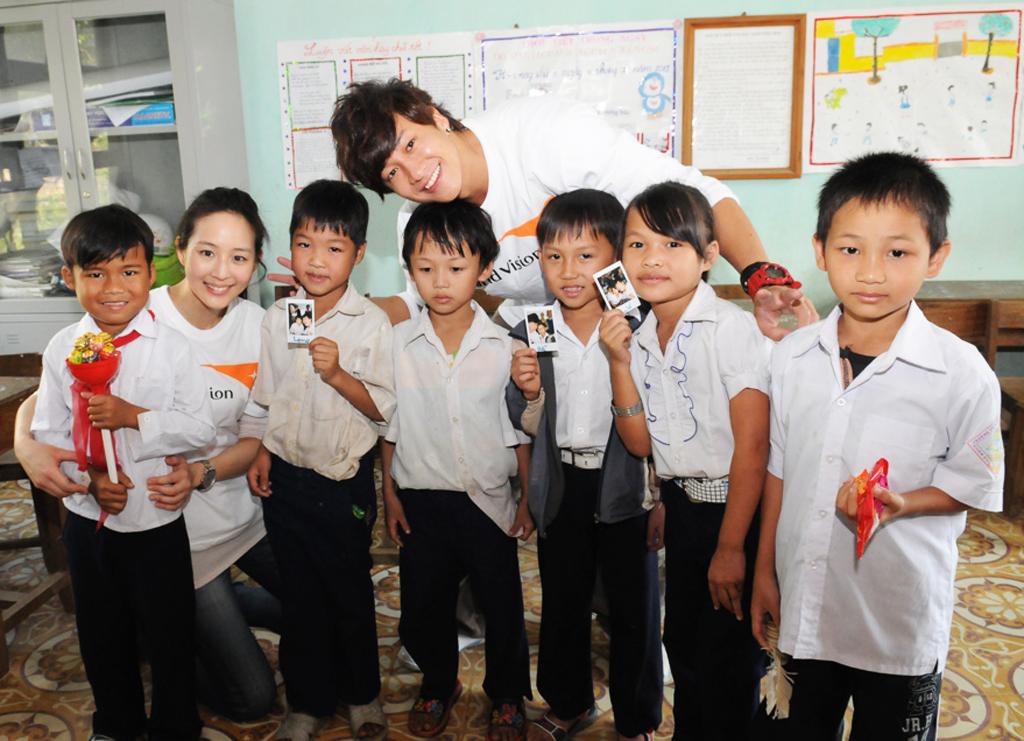 01代言人何潤東、張鈞甯與他們所資助的6名兒童在阮伯玉小學相見歡後合照(左一張鈞甯資助的兒童Ho,Van Truong),(其餘五名為潤東資助的兒童NGUYEN, Ngoc Luat,NGUYEN, Van Long,NGUYEN, Thi Lan,NGUYEN, Dinh