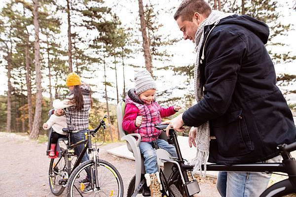 young-family-in-warm-clothes-cycling-in-autumn-PGVWZNA.jpg