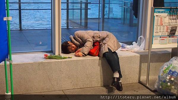 睡倒在路邊的人 旁邊那朵花, 是路人給的 哈