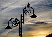 220px-Ammonite_lamp_post_at_dusk,_Lyme_Regis