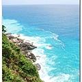 深藍色的海水,打到岸上形成白色的浪花,沿岸的水變成淺淺的藍