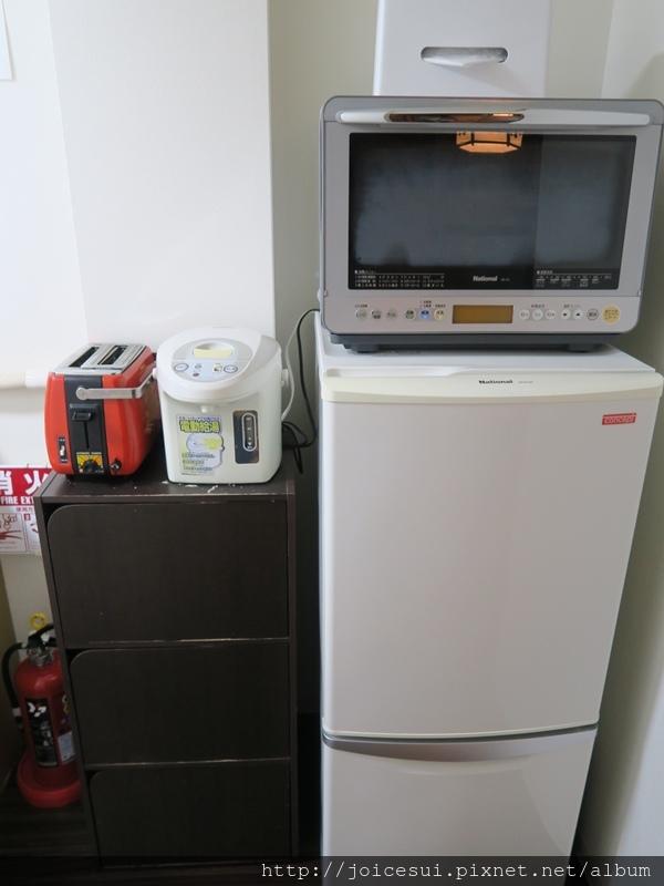 冰箱上有微波爐,還有熱水瓶和烤麵包機