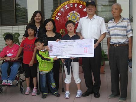 喜樂保育院院長林玉嫦及服務對象接受捐贈支票