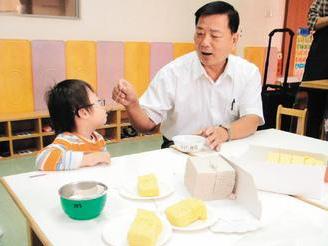 鹿港地政事務所主任顏明道與喜樂保育院服務對象一同享用蛋糕