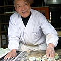 有著靦腆笑容的老先生,動作俐落的翻動著鐵板上的麻糬餅。