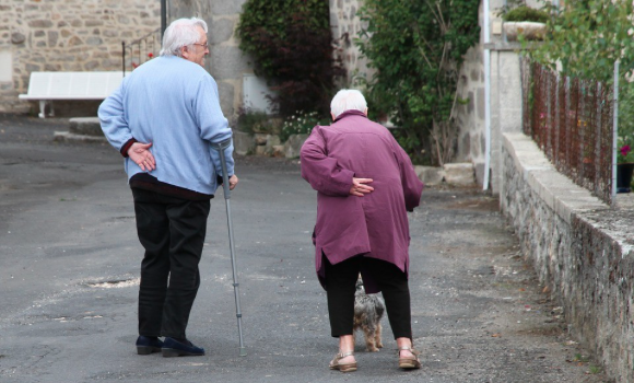 Image-of-an-elderly-couple-supporting-their-backs-and-walking-with-canes.-.png