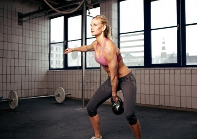 14157960-young-adult-fitness-woman-doing-swing-exercise-with-a-kettlebell-as-a-part-of-a-crossfit-workout