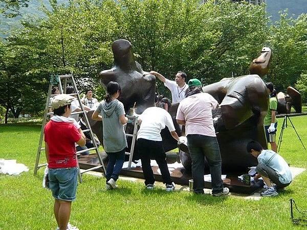 老師帶著學生們頂著烈日清理著雕像