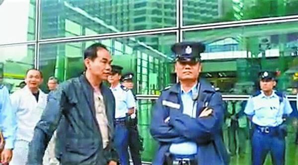 青關頭目洪偉成在與警方扯貓尾,軍裝警蹺埋雙手接受指示。
