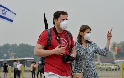 中國曾經是世界上被訪問最多的國家,今年出現旅遊人數急劇下降,空氣污染是主要原因之一。圖為2013年5月8日,北京,空氣污染嚴重,2名外國旅客戴上口罩。(Mark RALSTON/AFP)