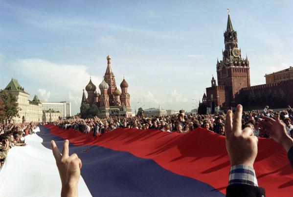 1991年8月22日,在莫斯科紅場,人們拿著一個巨大的俄羅斯國旗慶祝蘇共解體。(ANATOLY SAPRONENKOV / AFP)