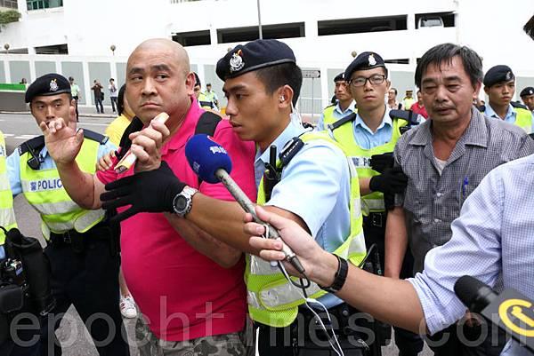 梁振英8月18日再次落區到觀塘出席論壇,各個政黨團體過千人到場抗議,圖為兩名梁振英的支持者涉嫌毆打抗議人士被捕。(潘在殊/大紀元)