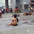 傷者衣服被炸飛,坐在路上等待救援。(網絡圖片)