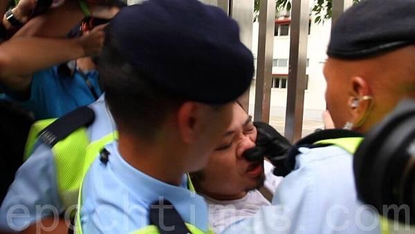 戴黑手套的警員強行把示威者拉走時,用手掩住其口鼻,又大力按其人中,令該示威者全身無力,一度昏厥,警員卻喝令他「不要咬差人」,有誣告之嫌。(蔡雯文/大紀元)