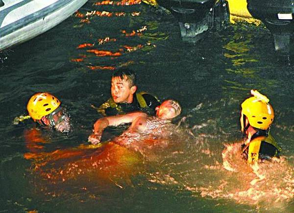 消防蛙人合力將重傷的胡興正送上岸。