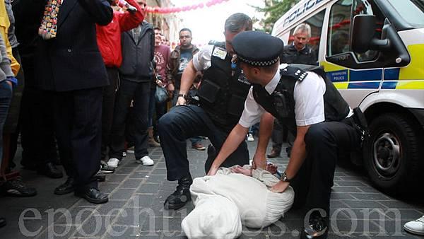 警方逮住攻擊法輪功學員的歹徒。(攝影:冠齊/大紀元)
