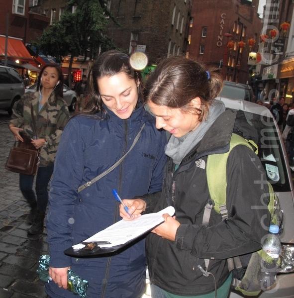 2013年9月15日,兩個西班牙女孩明白法輪功真相後,在制止中共活摘法輪功學員的請願書  上簽名。(攝影:肖民/大紀元)