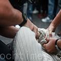 被抓獲的歹徒被警方戴上手銬。(攝影:Helen/大紀元)