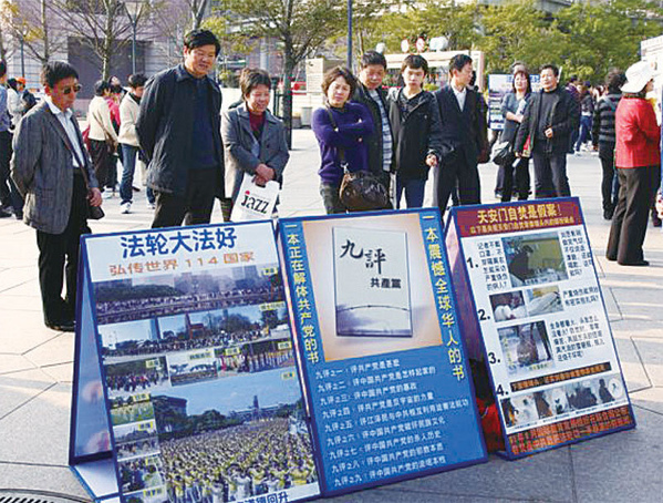 台灣法輪功學員在台北著名的景點101大樓前講真相,許多大陸觀光客目不轉睛的盯著真相展板看。(大紀元資料庫)