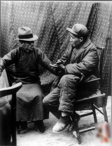 1938年1月,毛澤東在延安會見來訪的梁漱溟。毛左腿翹在椅子的扶手上,一副流氓模樣。