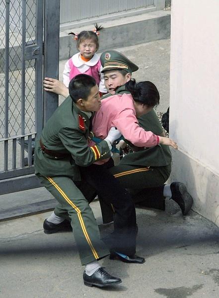 兩名中共武警從日本領事館內把李貴玉強行拽出,拉扯過程中,兩歲的韓美從媽媽的背上掉到地上後,站在那裏哭。(北韓人權聯合會主席文國韓提供)