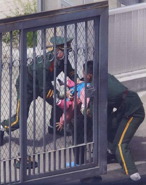 兩名中共武警從日本領事館內將背著韓美的母親李貴玉往外拉扯,過程中,武警的帽子都掉到了地上。(北韓人權聯合會主席文國韓提供)