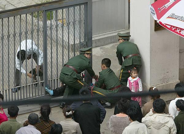 三名中共武警從領館內將已躺在地上韓美奶奶鄭慶淑往外拖。(北韓人權聯合會主席文國韓提供)